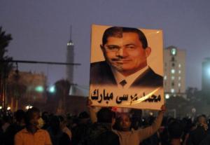 "An Egyptian protestor compares Hosni Mubarak (right) with Mohammed Morsi (left). The poster's caption reads ""Mohammed Morsi Mubarak""."